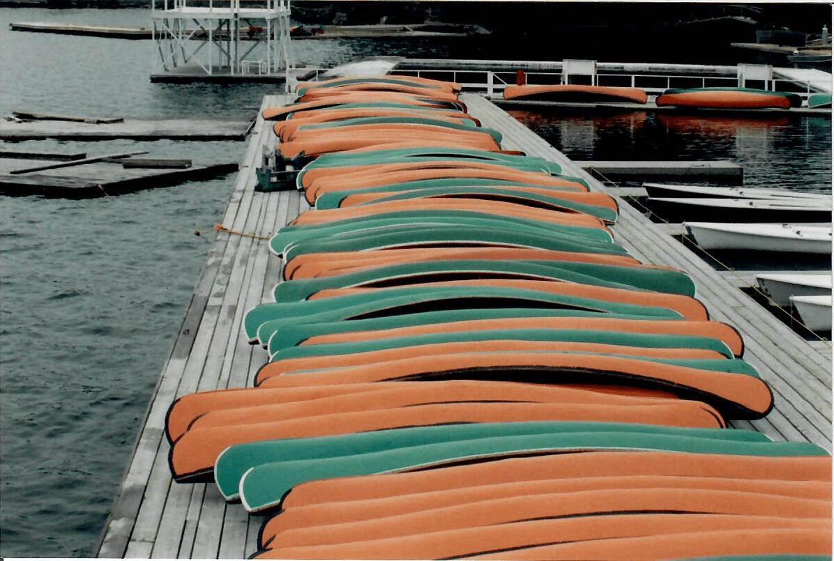 Ahmek and Wapomeo canoes lined up on the Ahmek dock.